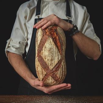 Handen man met een vers donker zelfgebakken brood