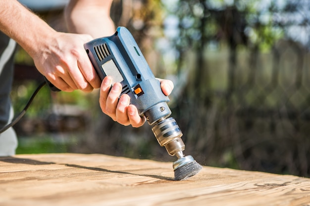 Handen man met elektrische roterende borstel metalen schijf een stuk hout schuren. houtbewerking buitenshuis.