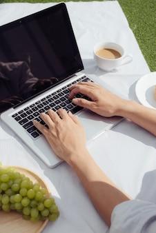 Handen man op laptop toetsenbord en koffie met donut. gemakkelijke werklevensstijl thuis in de ochtend.