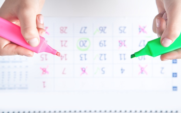 Handen markeert kalender met een marker.