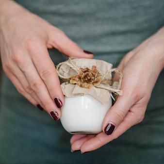 Handen meisje bedrijf in kleine potje huid crème of flessen lotion, natuurlijke cosmetica