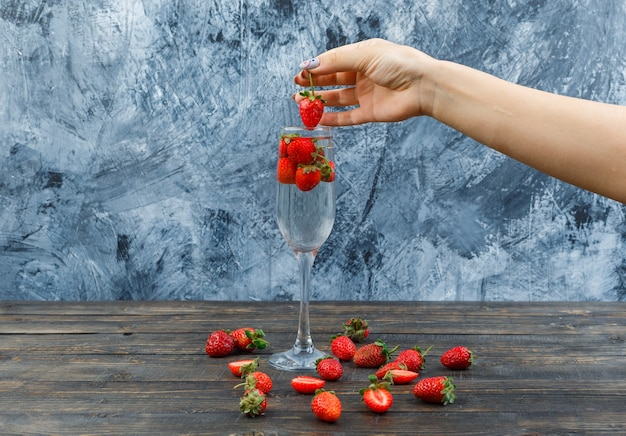 Handen met aardbeien op een houten bord