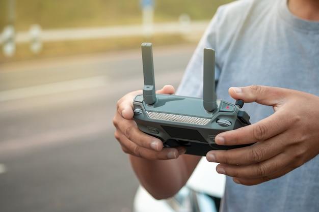 Handen met afstandsbediening van drone buiten.