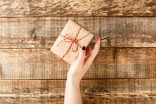 Handen met ambachtelijke papier geschenkdoos met als cadeau voor kerstmis, nieuwjaar op blauw, bovenaanzicht