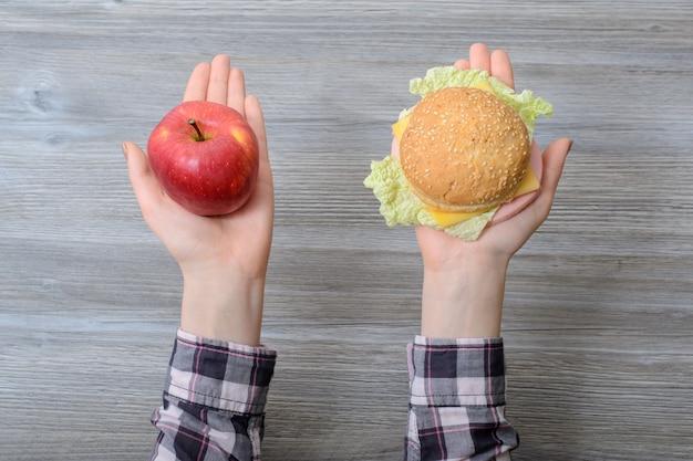 Handen met appel en hamburger