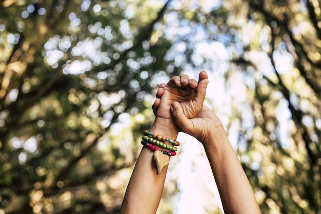 Handen met armband met hart en groene bosbomen