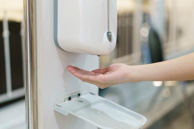 Handen met automatische ontsmettingsvloeistof spuitmachine, contactloze dispenser.