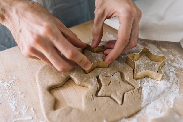 Handen met behulp van cookie cutter op gebak