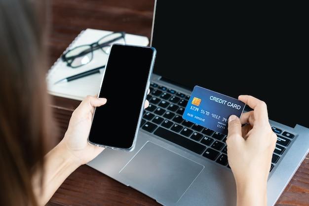 Handen met behulp van een mobiele telefoon terwijl u een creditcard voor de computer houdt