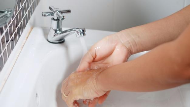 Handen met behulp van zeep en handen wassen onder de waterkraan