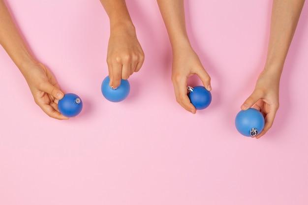 Handen met blauwe kerstbal ballen over lichtroze