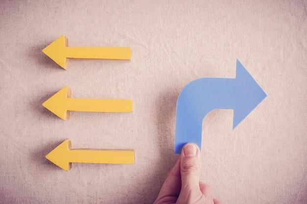 Handen met blauwe pijl naar tegenovergestelde richting van anderen