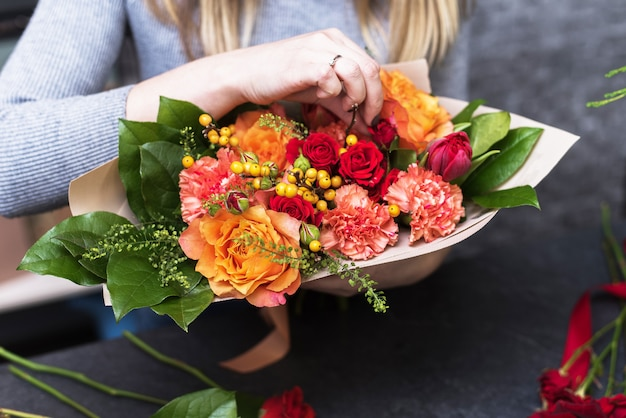 Handen met boeket van verschillende bloemen