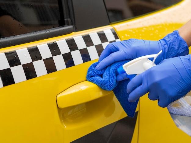Handen met chirurgische handschoen schoonmaken auto deur handvat