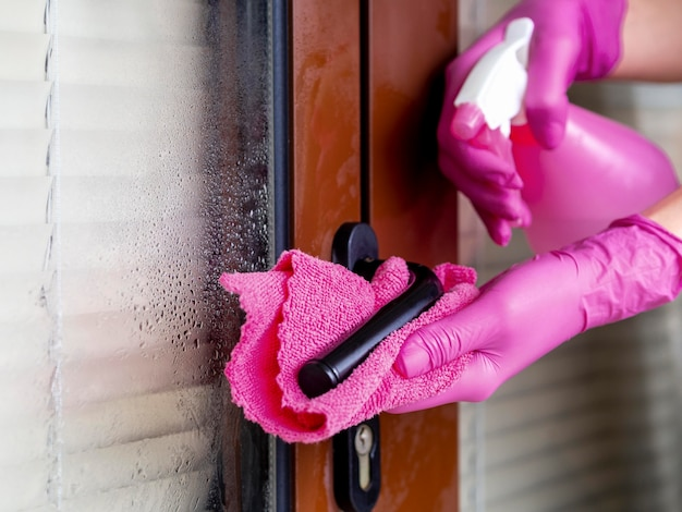 Handen met chirurgische handschoenen die deurhandvat met wassing schoonmaken