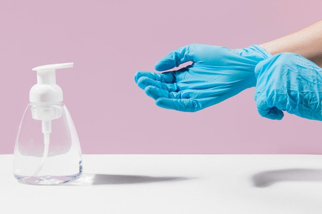 Handen met chirurgische handschoenen die handdesinfecterend middel gebruiken