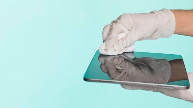 Handen met chirurgische handschoenen die tablet desinfecteren