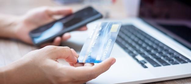 Handen met creditcard en gadgets voor online winkelen