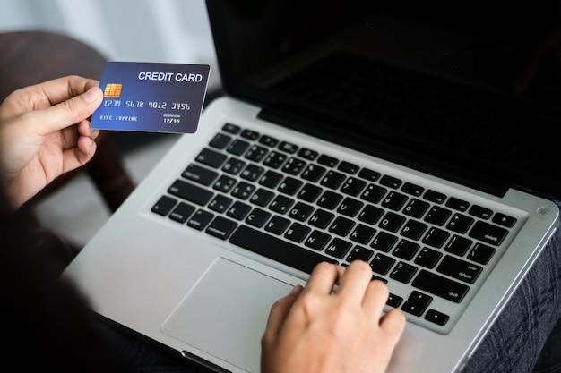 Handen met creditcard en met behulp van laptop. online winkelen. ruimte kopiëren.