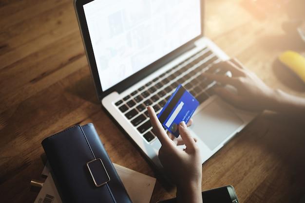 Handen met creditcard en met behulp van laptop.