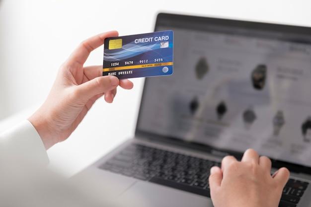 Handen met creditcard en met behulp van laptopcomputer, zakenvrouw thuis werken, online winkelen, e-commerce, zakgeld, internetbankieren.