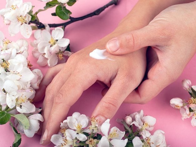 Handen met crème op een roze achtergrond met witte bloemen van apple close-up. huidverzorgingsproduct, schoonheid, handverzorging, spa.
