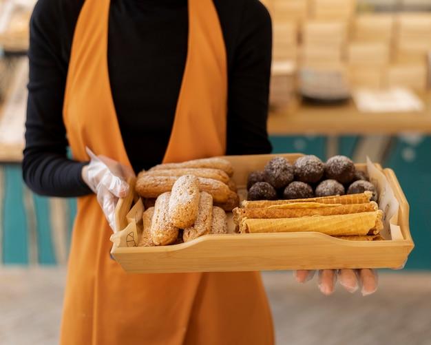 Handen met dienblad met dessert