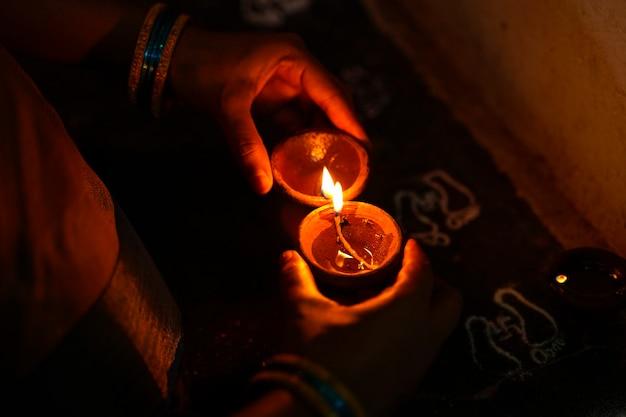 Handen met diwali-lampen
