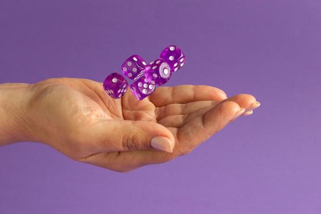 Handen met dobbelstenen op paarse achtergrond