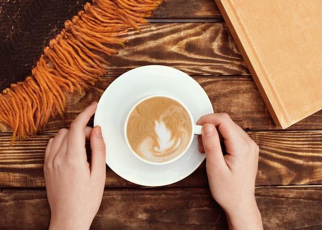 Handen met dop van koffie op een bordje, boek en wollen sjaal op houten achtergrond
