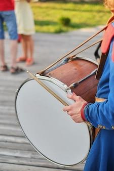 Handen met drumsticks en een grote drum nationale jurk