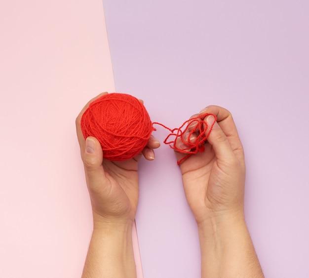 Handen met een bal van rode wollen draden