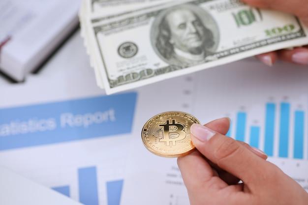 Handen met een bitcoin en een fan van dollars