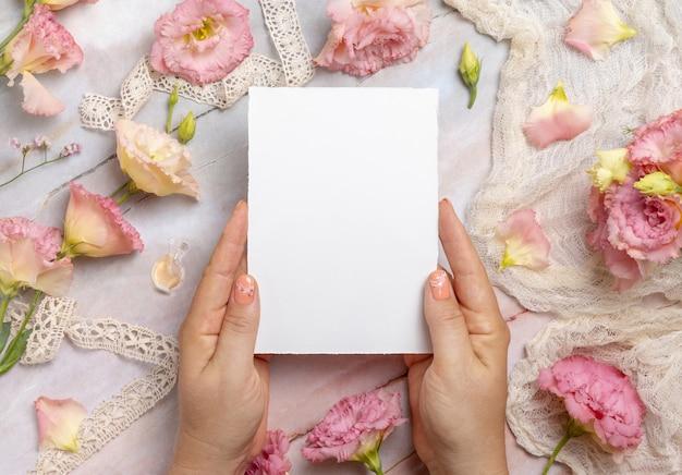Handen met een blanco kaart boven een marmeren tafel versierd met bloemen en linten