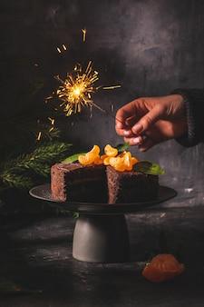 Handen met een brandend vuurwerk boven de taart
