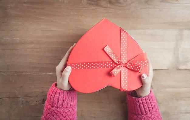 Handen met een doos in de vorm van hart op houten achtergrond.