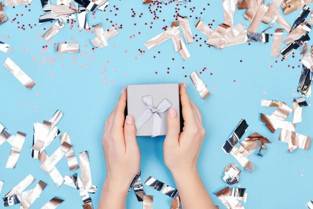Handen met een geschenk op een blauwe achtergrond en decoraties: sterren en metafaan. vakantieconcept - valentijnsdag, 8 maart, internationale vrouwendag, kerstmis. bovenaanzicht