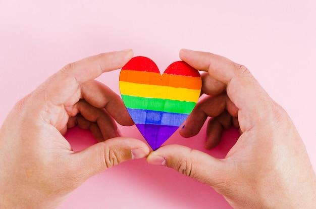 Handen met een hart met trots dag vlag kleuren