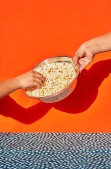 Handen met een kom popcorn.