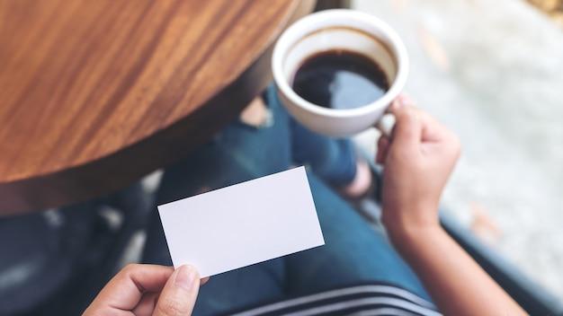 Handen met een lege visitekaartje en een koffiekopje