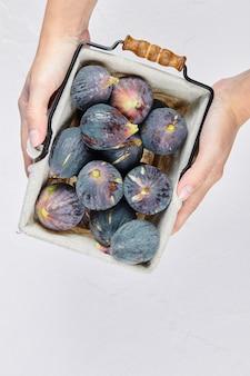 Handen met een mandje met paarse vijgen op wit