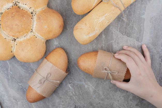 Handen met een minibroodje op marmeren oppervlak