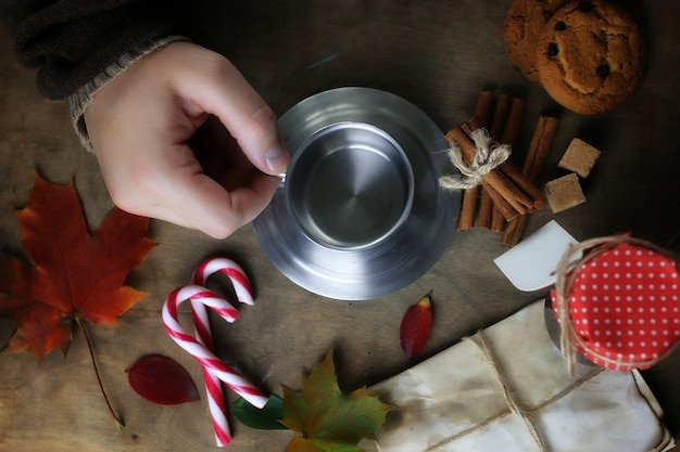 Handen met een mok hete koffie op een tafel met herfstbladeren