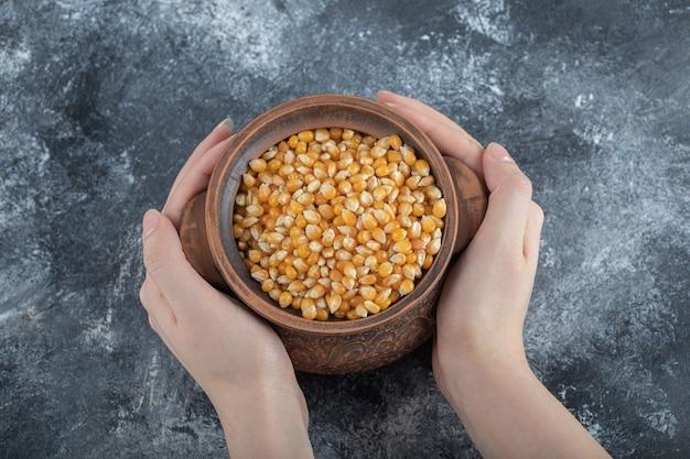 Handen met een oude kom vol met ongekookte popcornzaden.