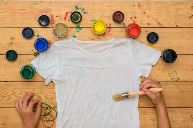 Handen met een penseel en verf schilderen een wit t-shirt