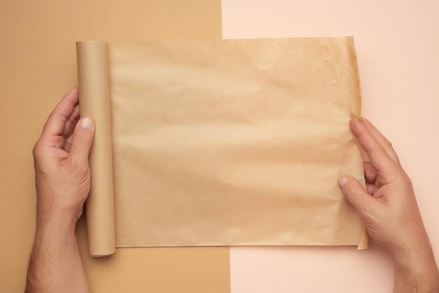 Handen met een rol bruin papier