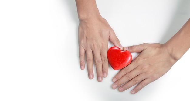 Handen met een rood hart. hart gezondheid. en donatieconcepten