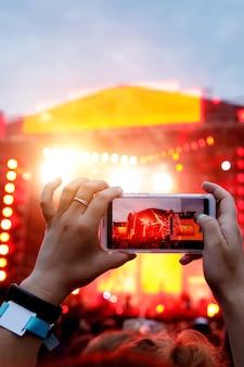 Handen met een smartphone neemt live muziekfestival, live concert, live concert op.