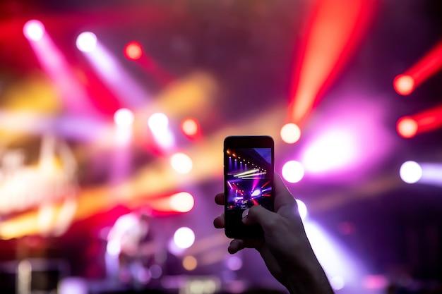 Handen met een smartphone neemt live muziekfestival, live concert op