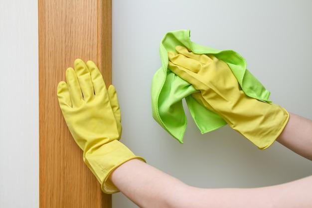 Handen met een stofdoek die de deur schoonmaken